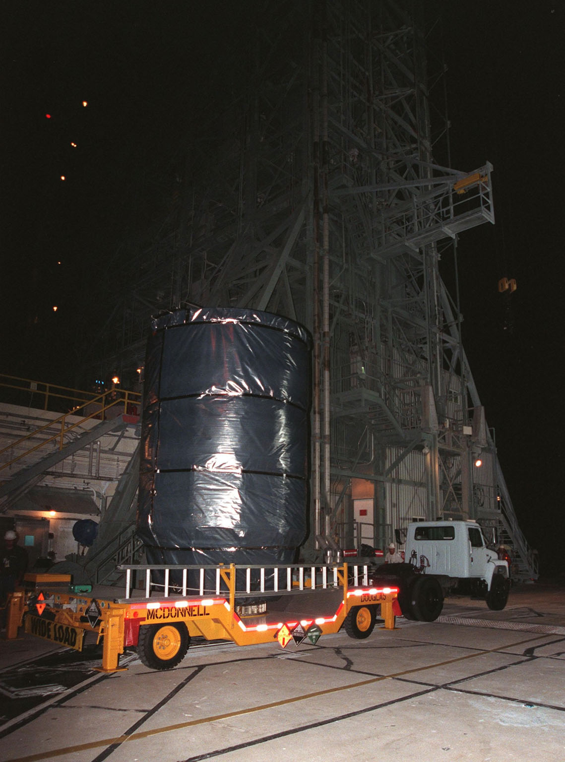 In the early morning, the Stardust spacecraft, with the third stage of a Boeing Delta II rocket attached, arrives atop a transporter at Launch Pad 17-A, Cape Canaveral Air Station. The second and third stages of the rocket will be mated and prepared for liftoff on Feb. 6. Stardust is destined for a close encounter with the comet Wild 2 in January 2004. Using a silicon-based substance called aerogel, Stardust will capture comet particles flying off the nucleus of the comet. The spacecraft also will bring back samples of interstellar dust. These materials consist of ancient pre-solar interstellar grains and other remnants left over from the formation of the solar system. Scientists expect their analysis to provide important insights into the evolution of the sun and planets and possibly into the origin of life itself. The collected samples will return to Earth in a sample return capsule to be jettisoned as Stardust swings by Earth in January 2006