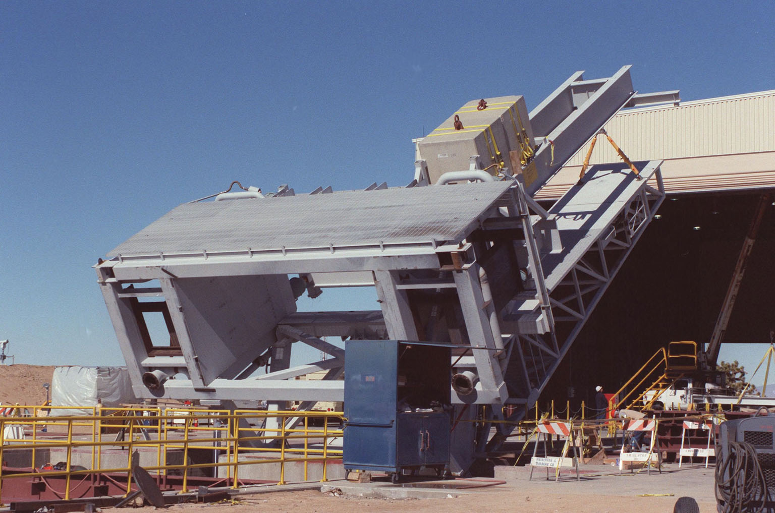 """The KSC-developed X-33 weight simulator (top), known as the """"iron bird,"""" is lifted to a vertical position at the X-33 launch site as part of launch equipment testing on Edwards Air Force Base, CA. The simulator matches the 75,000-pound weight and 63-foot height of the X-33 vehicle that will be using the launch equipment. KSC's Vehicle Positioning System (VPS) placed the simulator on the rotating launch platform prior to the rotation. The new VPS will dramatically reduce the amount of manual labor required to position a reusable launch vehicle for liftoff"""