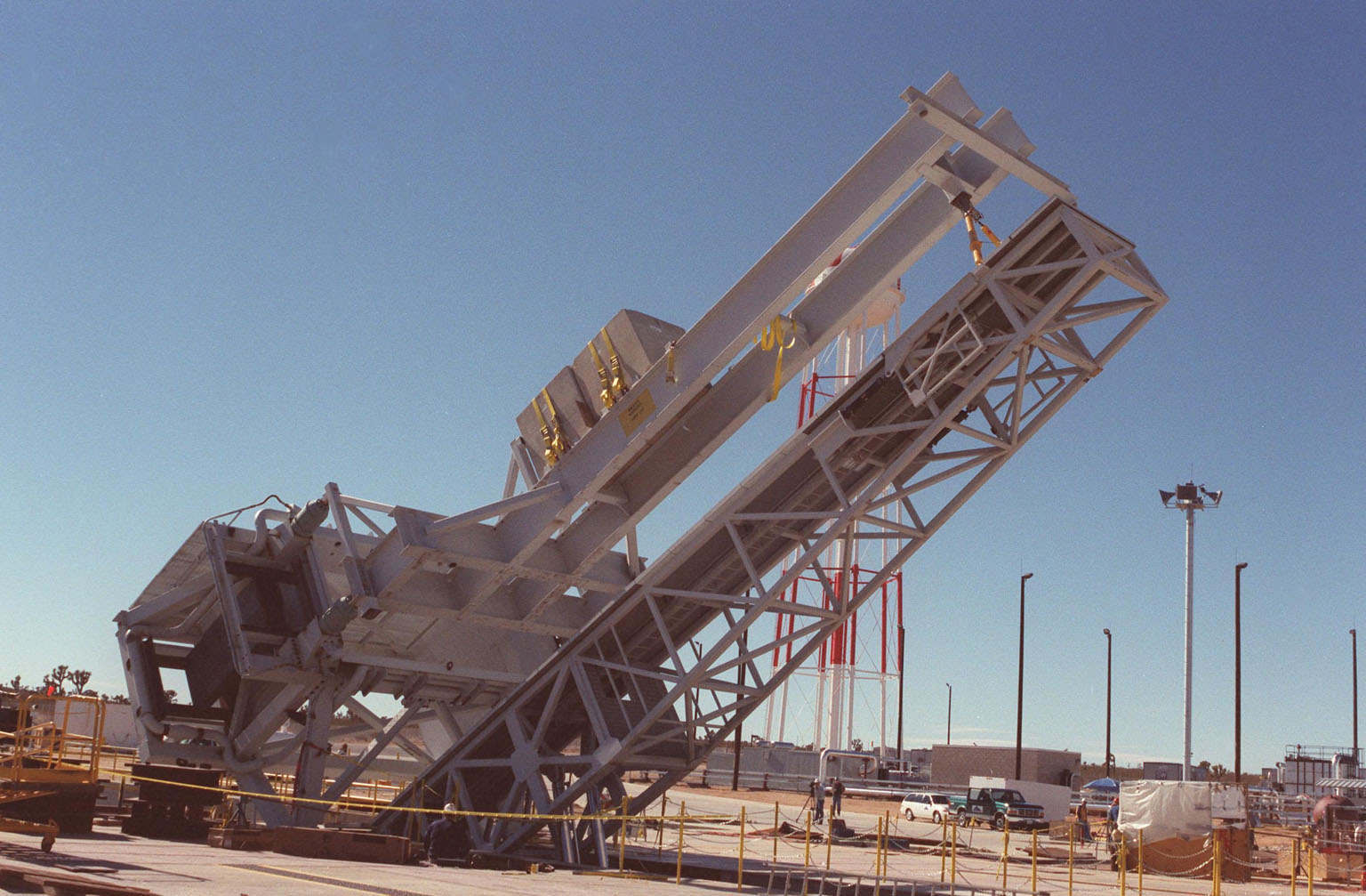 """As part of X-33 launch equipment testing at Edwards Air Force Base, CA, the KSC-developed X-33 weight simulator (top), known as the """"iron bird,"""" is lifted to a vertical position at the X-33 launch site. The simulator matches the 75,000-pound weight and 63-foot height of the X-33 vehicle that will be using the launch equipment. KSC's Vehicle Positioning System (VPS) placed the simulator on the rotating launch platform prior to the rotation. The new VPS will dramatically reduce the amount of manual labor required to position a reusable launch vehicle for liftoff"""