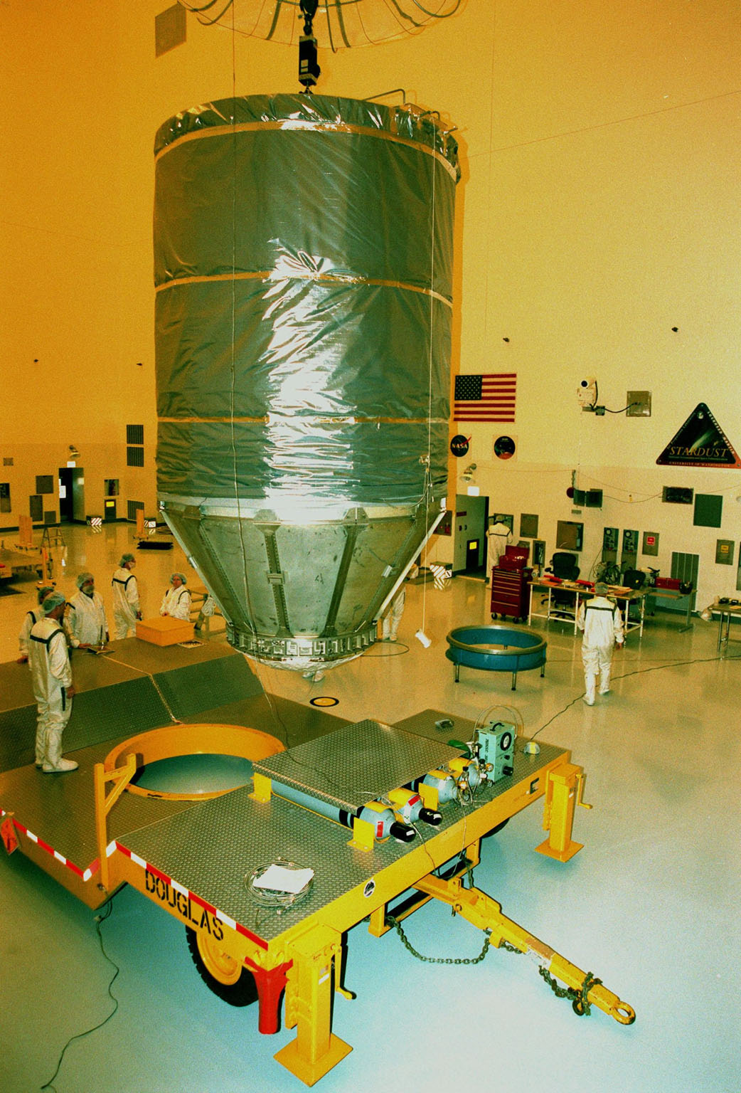 Completely enclosed in a protective canister, the spacecraft Stardust is moved by a crane toward a transporter in the Payload Hazardous Servicing Facility. Stardust is being moved to Launch Pad 17-A, Cape Canaveral Air Station, for launch preparations. The spacecraft is targeted for liftoff on Feb. 6 aboard a Boeing Delta II rocket for a close encounter with the comet Wild 2 in January 2004. Using a silicon-based substance called aerogel, Stardust will capture comet particles flying off the nucleus of the comet. The spacecraft also will bring back samples of interstellar dust. These materials consist of ancient pre-solar interstellar grains and other remnants left over from the formation of the solar system. Scientists expect their analysis to provide important insights into the evolution of the sun and planets and possibly into the origin of life itself. The collected samples will return to Earth in a sample return capsule to be jettisoned as Stardust swings by Earth in January 2006