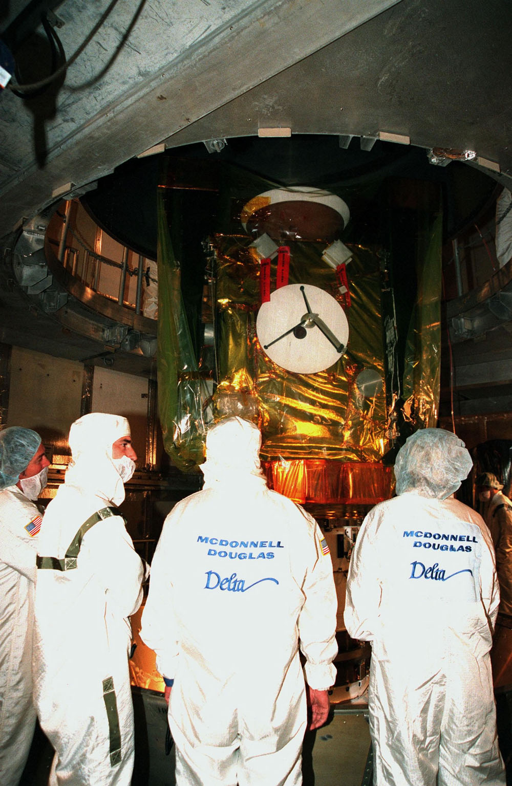 Workers watch as the protective canister surrounding the Stardust spacecraft is removed at Launch Pad 17-A, Cape Canaveral Air Station. Preparations continue for liftoff of the Boeing Delta II rocket carrying Stardust on Feb. 6. Stardust is destined for a close encounter with the comet Wild 2 in January 2004. Using a silicon-based substance called aerogel, Stardust will capture comet particles flying off the nucleus of the comet. The spacecraft also will bring back samples of interstellar dust. These materials consist of ancient pre-solar interstellar grains and other remnants left over from the formation of the solar system. Scientists expect their analysis to provide important insights into the evolution of the sun and planets and possibly into the origin of life itself. The collected samples will return to Earth in a sample return capsule to be jettisoned as Stardust swings by Earth in January 2006