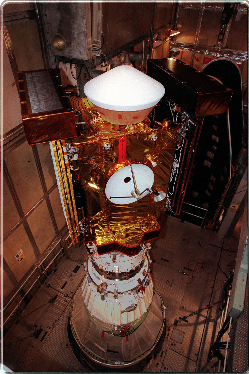 At Launch Pad 17-A, Cape Canaveral Air Station, the Stardust spacecraft waits for installation of the fairing (behind, right) that will enclose the spacecraft and the upper stage of the Boeing Delta II rocket. Targeted for launch at 4:06:42 p.m. on Feb. 6, Stardust is destined for a close encounter with the comet Wild 2 in January 2004. Using a silicon-based substance called aerogel, Stardust will capture comet particles flying off the nucleus of the comet. The spacecraft also will bring back samples of interstellar dust. These materials consist of ancient pre-solar interstellar grains and other remnants left over from the formation of the solar system. Scientists expect their analysis to provide important insights into the evolution of the sun and planets and possibly into the origin of life itself. The collected samples will return to Earth in a sample return capsule to be jettisoned as Stardust swings by Earth in January 2006