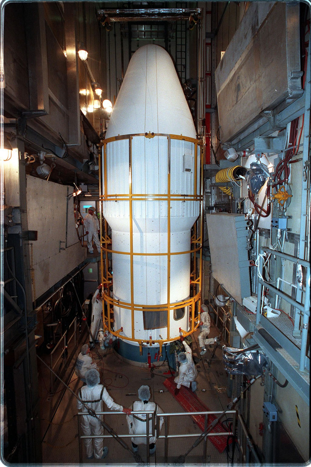 At Launch Pad 17-A, Cape Canaveral Air Station, workers check the lower fittings of the fairing installed around the Stardust spacecraft and upper stage of the Boeing Delta II rocket. Targeted for launch at 4:06:42 p.m. on Feb. 6, the spacecraft is destined for a close encounter with the comet Wild 2 in January 2004. Using a silicon-based substance called aerogel, Stardust will capture comet particles flying off the nucleus of the comet. The spacecraft also will bring back samples of interstellar dust. These materials consist of ancient pre-solar interstellar grains and other remnants left over from the formation of the solar system. Scientists expect their analysis to provide important insights into the evolution of the sun and planets and possibly into the origin of life itself. The collected samples will return to Earth in a sample return capsule to be jettisoned as Stardust swings by Earth in January 2006