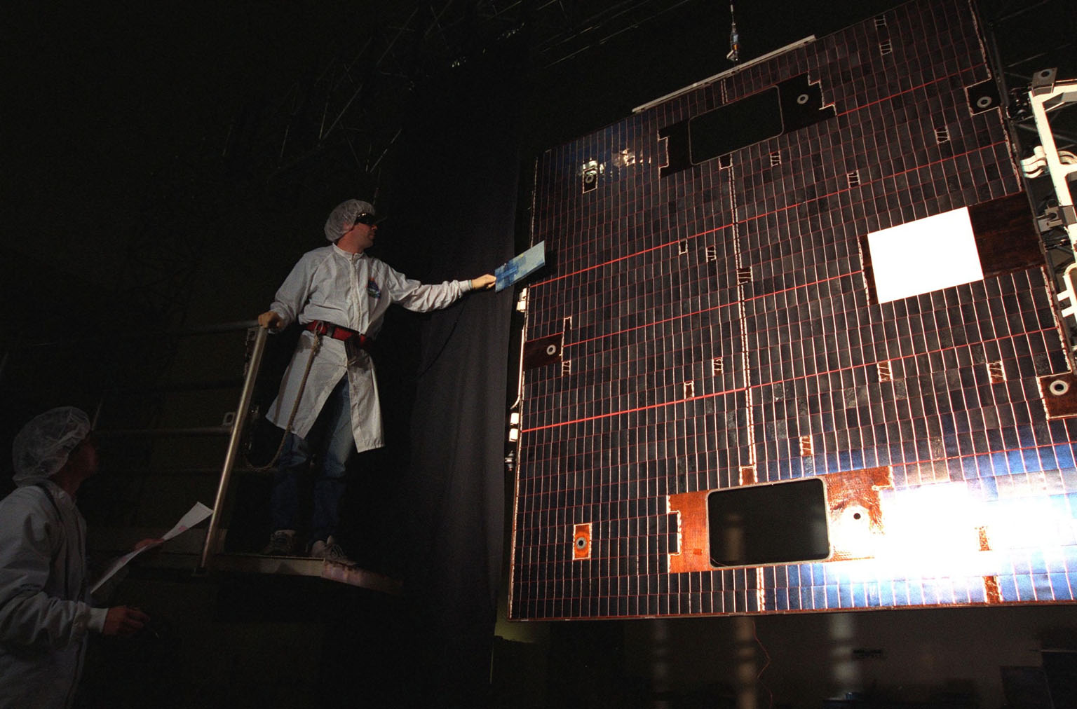 During an illumination test, a Loral worker at Astrotech, Titusville, Fla., verifies circuitry on the solar panel of the GOES-L [ http://www-pao.ksc.nasa.gov/kscpao/captions/subjects/goes-l.htm ] weather satellite. The satellite is to be launched from Cape Canaveral Air Station aboard an Atlas II rocket in late March. The GOES-L is the fourth of a new advanced series of geostationary weather satellites for the National Oceanic and Atmospheric Administration. It is a three-axis inertially stabilized spacecraft that will provide pictures and perform atmospheric sounding at the same time. Once launched, the satellite, to be designated GOES-11, will undergo checkout and provide backup capabilities for the existing, aging GOES East weather satellite
