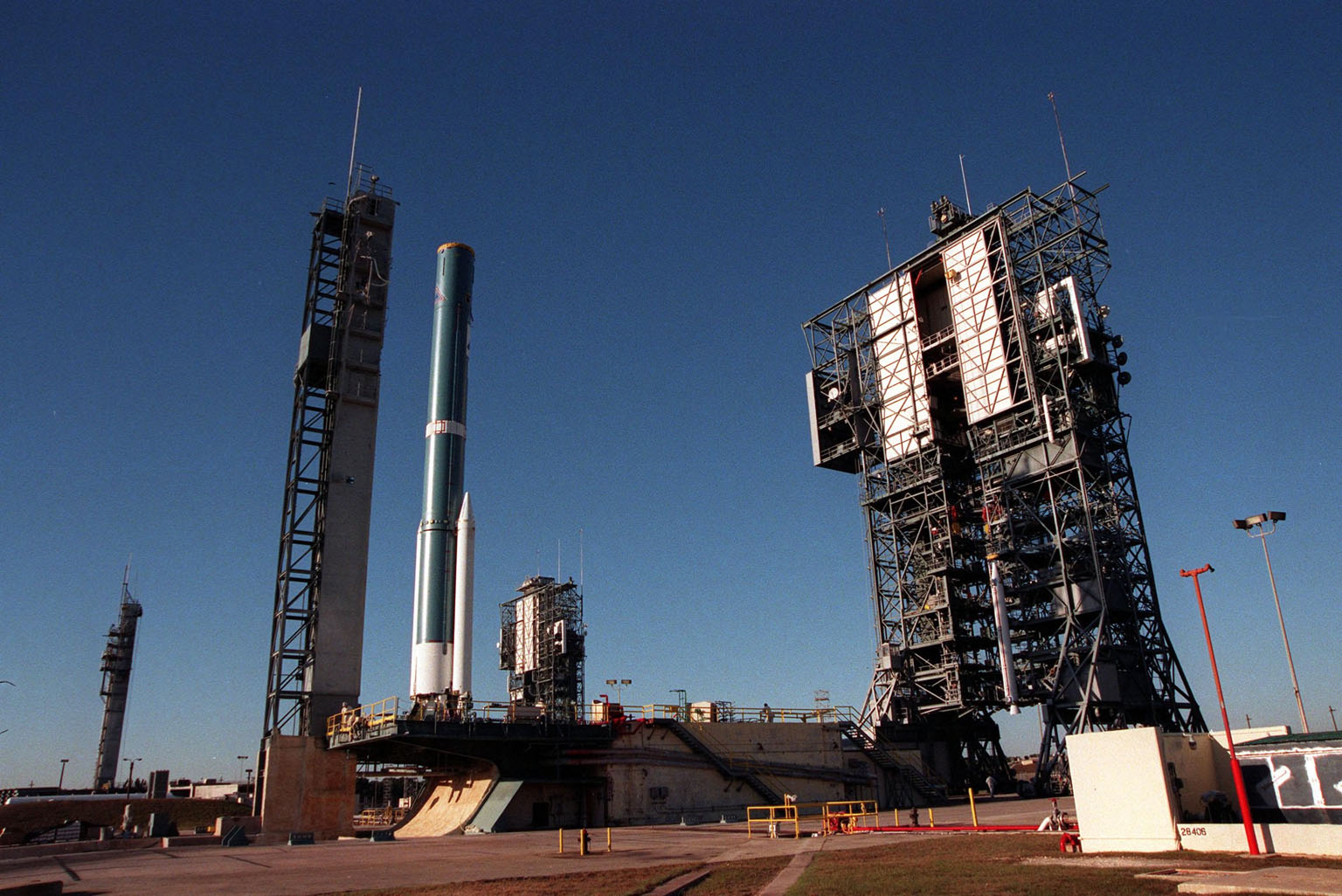 A Boeing Delta II rocket sits on Launch Pad 17A (left), Cape Canaveral Air Station, before mating with its final Solid Rocket Booster, in the tower at right. In the background is Pad 17B with its two launch tower components. The Delta II rocket will carry the Stardust satellite into space for a close encounter with the comet Wild 2 in January 2004. Using a medium called aerogel, Stardust will capture comet particles flying off the nucleus of the comet, plus collect interstellar dust for later analysis. The collected samples will return to Earth in a Sample Return Capsule to be jettisoned as Stardust swings by Earth in January 2006. Stardust is scheduled to be launched on Feb. 6, 1999