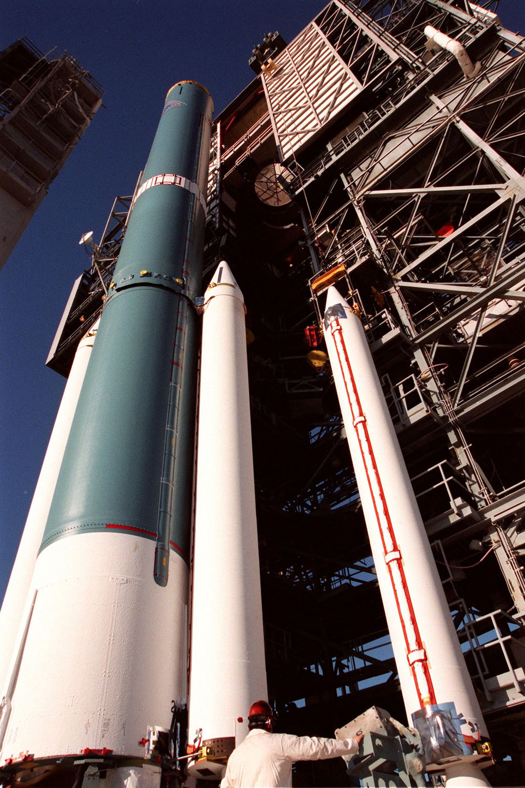 At Pad 17A, Cape Canaveral Air Station, a fourth and final solid rocket booster (SRB) (right) is moved from the mobile tower by a crane before mating with the Delta II rocket (left). The rocket will be aided by four SRBs to carry the Stardust satellite into space for a close encounter with the comet Wild 2 in January 2004. Using a medium called aerogel, Stardust will capture comet particles flying off the nucleus of the comet, plus collect interstellar dust for later analysis. The collected samples will return to Earth in a Sample Return Capsule to be jettisoned as Stardust swings by Earth in January 2006. Stardust is scheduled to be launched on Feb. 6, 1999