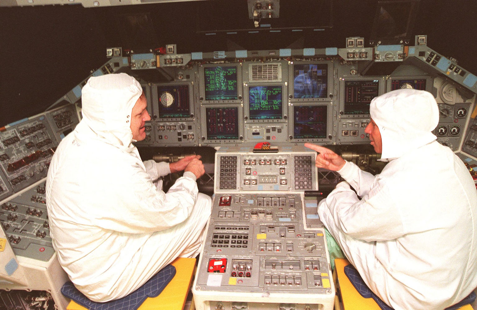 STS-101 Commander James Halsell (left) and STS-98 Commander Ken Cockrell (right) look over the recently installed Multifunction Electronic Display Subsystem (MEDS) in the cockpit of the orbiter Atlantis, which each will command on their upcoming respective missions. The new full-color, flat panel MEDS improves crew/orbiter interaction with easy-to-read, graphic portrayals of key flight indicators like attitude display and mach speed. The installation makes Atlantis the most modern orbiter in the fleet and equals the systems on current commercial jet airliners and military aircraft. . The first flight of the upgraded Atlantis is STS-101, scheduled for launch in December 1999; the second flight, STS-98, is scheduled for launch in April 2000