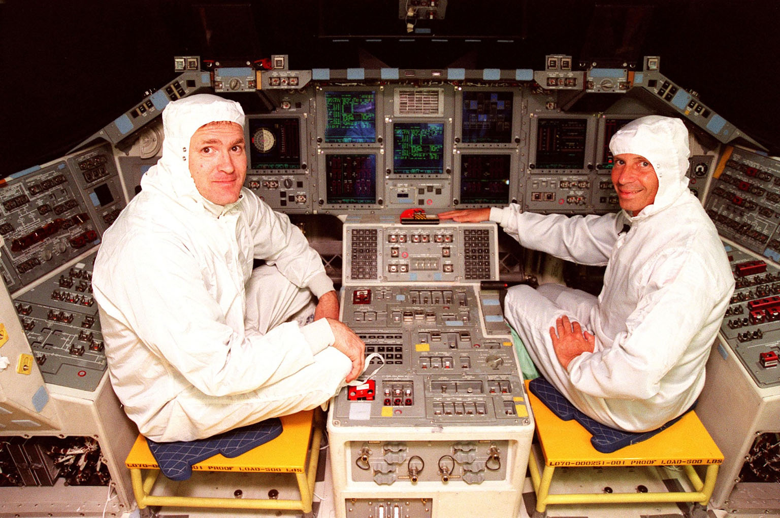 STS-101 Commander James Halsell (left) and STS-98 Commander Ken Cockrell (right) pause for a photo while looking over the recently installed Multifunction Electronic Display Subsystem (MEDS) in the cockpit of the orbiter Atlantis. The new full-color, flat panel MEDS improves crew/orbiter interaction with easy-to-read, graphic portrayals of key flight indicators like attitude display and mach speed. The installation makes Atlantis the most modern orbiter in the fleet and equals the systems on current commercial jet airliners and military aircraft. The first flight of the upgraded Atlantis is STS-101, scheduled for launch in December 1999; the second flight, STS-98, is scheduled for launch in April 2000