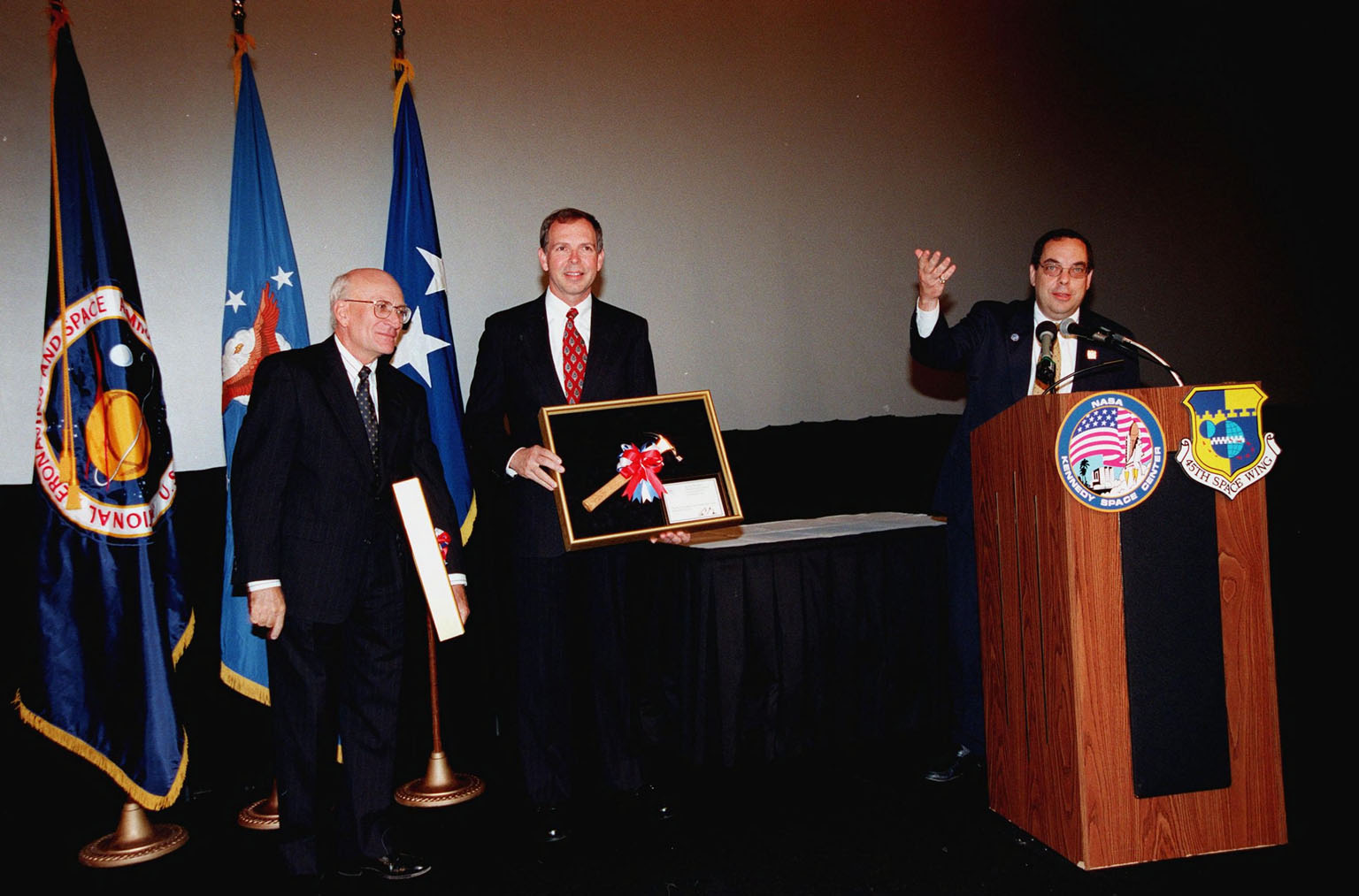 Ed Gormel (left) and Chris Fairey (center) display the Hammer Award they received at a special presentation in the IMAX 2 Theater in the Kennedy Space Center Visitor Complex. The Hammer Award is Vice President Al Gore's special recognition of teams of federal employees who have made significant contributions in support of the principles of the National Partnership for Reinventing Government. At the podium is Morley Winograd director of the National Partnership for Reinventing Government, who presented the award. This Hammer Award acknowledges the accomplishments of a joint NASA and Air Force team that established the Joint Base Operations and Support Contract (J-BOSC) Source Evaluation Board (SEB). Fairey and Gormel are co-chairs of the SEB. The team developed and implemented the acquisition strategy for establishing a single set of base operations and support service requirements for KSC, Cape Canaveral Air Station and Patrick Air Force Base