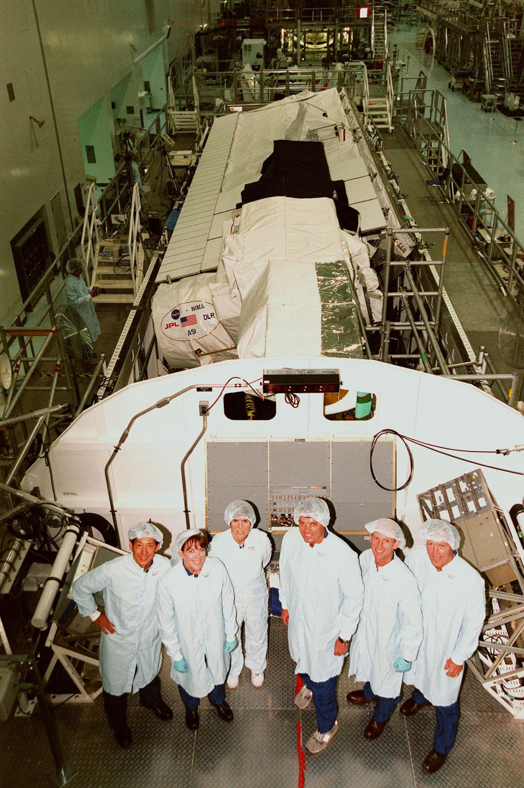 In the Space Station Processing Facility, the STS-99 crew pose in front of the Shuttle Radar Topography Mission, the payload for their mission. From left are Mission Specialists Mamoru Mohri of Japan, Janet Lynn Kavandi (Ph.D.), and Janice Voss (Ph.D.); Commander Kevin R. Kregel; Mission Specialist Gerhard Thiele of Germany; and Pilot Dominic L. Pudwill Gorie. Mohri represents the National Space Development Agency of Japan and Thiele represents the European Space Agency. An international project spearheaded by the National Imagery and Mapping Agency and NASA, with participation of the German Aerospace Center DLR, the SRTM consists of a specially modified radar system that will gather data for the most accurate and complete topographic map of the Earth's surface that has ever been assembled. SRTM will make use of radar interferometry, wherein two radar images are taken from slightly different locations. Differences between these images allow for the calculation of surface elevation, or change. The SRTM hardware will consist of one radar antenna in the shuttle payload bay and a second radar antenna attached to the end of a mast extended 60 meters (195 feet) out from the shuttle. STS-99 is scheduled to launch Sept. 16 at 8:47 a.m. from Launch Pad 39A