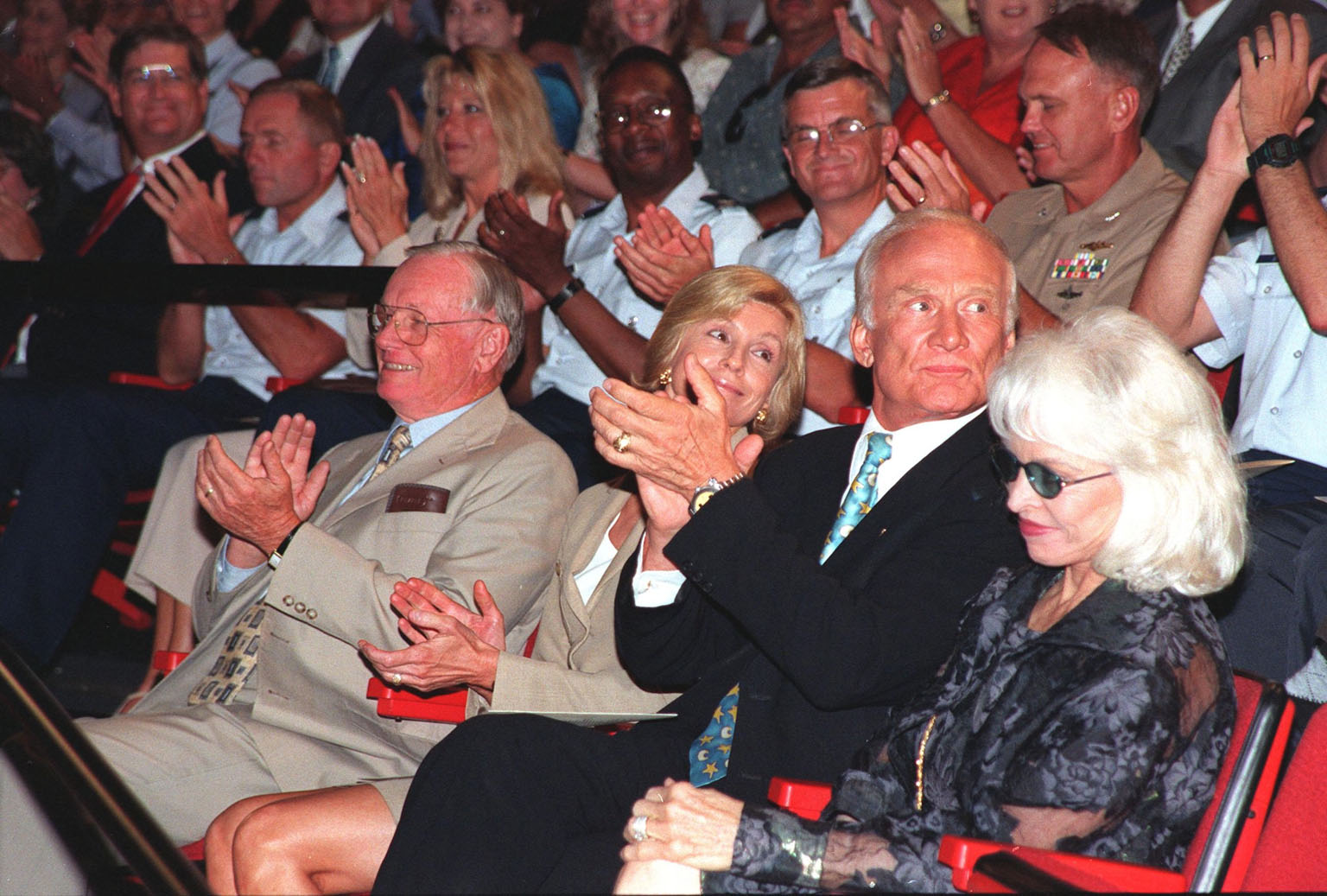 """At a special presentation of the Hammer Award in the IMAX 2 Theater in the Kennedy Space Center Visitor Complex, former Apollo astronauts Neil Armstrong (left) and Edwin """"Buzz"""" Aldrin (second from right) applauded the recipients, Kennedy Space Center and the 45th Space Wing. The Hammer Award is Vice President Al Gore's special recognition of teams of federal employees who have made significant contributions in support of the principles of the National Partnership for Reinventing Government. This Hammer Award acknowledges the accomplishments of a joint NASA and Air Force team that established the Joint Base Operations and Support Contract (J-BOSC) Source Evaluation Board (SEB). Ed Gormel and Chris Fairey, co-chairs of the SEB, accepted the awards for the SEB. The team developed and implemented the acquisition strategy for establishing a single set of base operations and support service requirements for KSC, Cape Canaveral Air Station and Patrick Air Force Base. Armstrong and Aldrin were at KSC to attend a banquet and other activities for the 30th anniversary of the Apollo 11 mission, which landed the first man on the moon"""