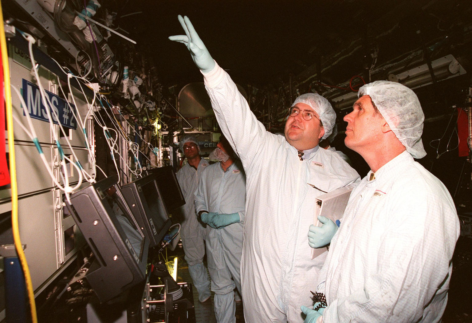 """KENNEDY SPACE CENTER, FLA. -- In the Space Station Processing Facility, Thomas R. """"Randy"""" Galloway, with the Space Station Hardware Integration Office, points out a feature to U.S. Rep. Dave Weldon (right) in the U.S. Lab, called """"Destiny."""" In the far background is Dana Gartzke, the congressman's chief of staff. Weldon is on the House Science Committee and vice chairman of the Space and Aeronautics Subcommittee. Destiny is scheduled to be launched on Space Shuttle Endeavour in early 2000. It will become the centerpiece of scientific research on the ISS, with five equipment racks aboard to provide essential functions for station systems, including high data-rate communications, and to maintain the station's orientation using control gyroscopes launched earlier. Additional equipment and research racks will be installed in the laboratory on subsequent Shuttle flights"""