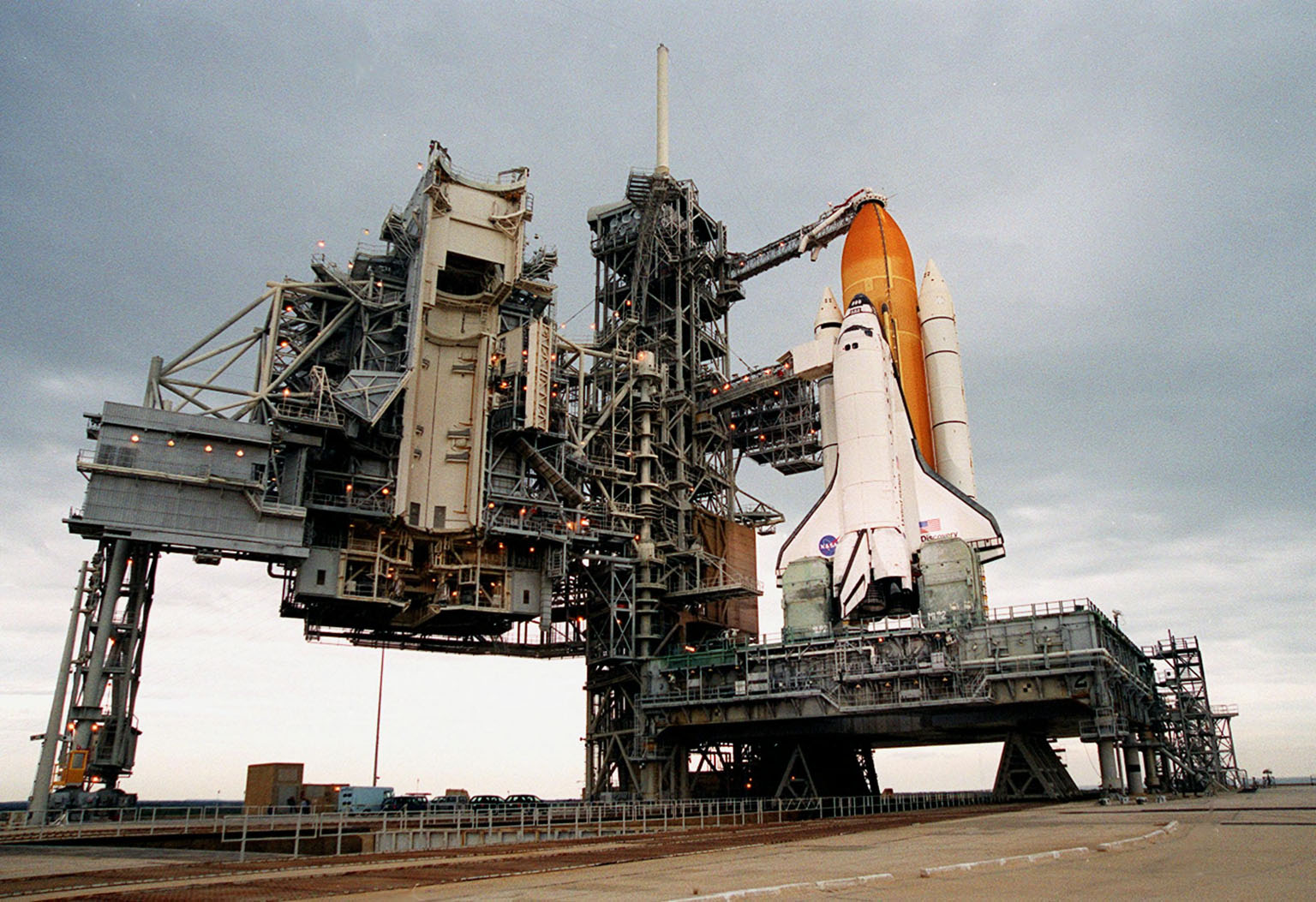 After rollback of the Rotating Service Structure at Launch Pad 39B (left) before dawn, the Space Shuttle Discovery is revealed poised for flight on mission STS-103. The rollback of the structure was complete at 4:46 a.m. EST. STS-103 is scheduled for launch Dec. 16 at 9:18 p.m. EST. The mission is expected to last about 9 days and 21 hours with a landing at KSC Sunday, Dec. 26, at 6:56 p.m. EST