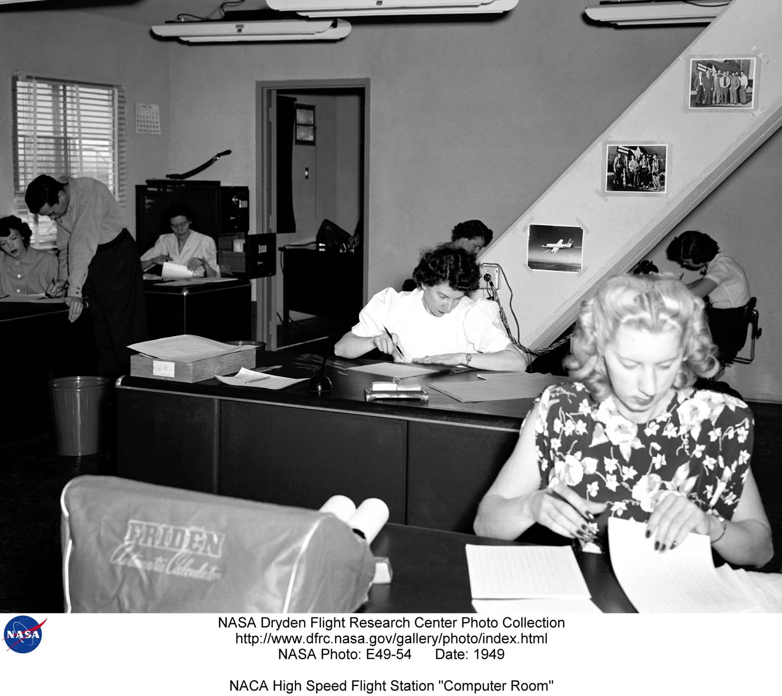 """Early """"computers"""" at work, summer 1949. In the terminology of that period, computers were employees--typically female--who performed the arduous task of transribing raw data from roles of celluloid film and strips of oscillograph paper and then, using slide rules and electric calculators, reducing it to standard engineering units. Note mechanical calculator with Friden cover at left. The users named them """"Galloping Gerties"""" because of their movement when in use. They used pads under them to cushion the motion. Seen here, left side, front to back, Mary (Tut) Hedgepeth, John Mayer and Emily Stephens. Right side, front to back, Lilly Ann Bajus, Roxanah Yancey, Gertrude (Trudy) Valentine (behind Roxanah), and Ilene Alexander."""