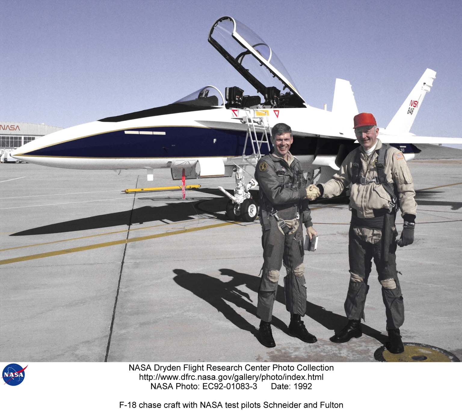 """Ed Schneider, (left), is the project pilot for the F-18 High Angle of Attack program at NASA's Dryden Flight Research Center, Edwards, California. He has been a NASA research pilot at Dryden since 1983. In addition to his assignment with the F-18 High Angle of Attack program, Schneider is a project pilot for the F-15B aeronautical research aircraft, the NASA NB-52B launch aircraft, and the SR-71 """"Blackbird"""" aircraft. He is a Fellow and was the 1994 President of the Society of Experimental Test Pilots. In 1996 he was awarded the NASA Exceptional Service Medal. Schneider is seen here with Fitzhugh L. Fulton Jr., (right), who was a civilian research pilot at Dryden. from August 1, 1966, until July 3, 1986, following 23 years of service as a pilot in the U.S. Air Force. Fulton was the project pilot on all early tests of the 747 Shuttle Carrier Aircraft (SCA) used to air launch the Space Shuttle prototype Enterprise in the Approach and Landing Tests (ALT) at Dryden in l977. For his work in the ALT program, Fulton received NASA's Exceptional Service Medal. He also received the Exceptional Service Medal again in 1983 for flying the 747 SCA during the European tour of the Space Shuttle Enterprise. During his career at Dryden, Fulton was project pilot on NASA's NB-52B launch aircraft used to air launch a variety of piloted and unpiloted research aircraft, including the X-15s and lifting bodies. He flew the XB-70 prototype supersonic bomber on both NASA-USAF tests and NASA research flights during the late 1960s, attaining speeds exceeding Mach 3. He was also a project pilot on the YF-12A and YF-12C research program from April 14, 1969, until September 25, 1978. The F/A-18 Hornet seen behind them is used primarily as a safety chase and support aircraft at NASA's Dryden Flight Research Center, Edwards, Calif. As support aircraft, the F-18's are used for safety chase, pilot proficiency and aerial photography. As a safety chase aircraft, F-18's, flown by research pilots, accompan"""